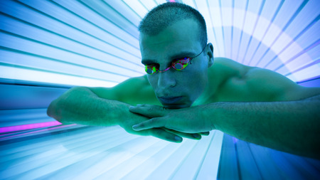 tanning: Handsome man with protect glasses in tanning booth Stock Photo