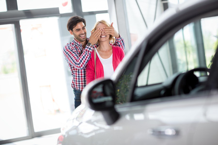 car salesperson: Couple stand in front of new car, man holding his wife covered her eyes