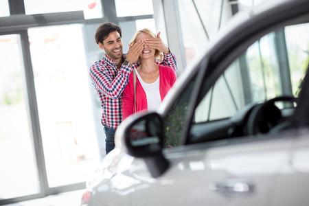 Paar staan voor nieuwe auto, man die zijn vrouw bedekt haar ogen
