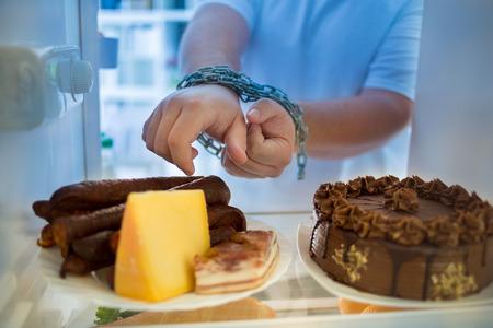 밤에 중량이 초과 된 사람은 다이어트 위기와 지방 소시지를 먹고 싶어한다. 스톡 콘텐츠
