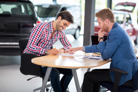 new car: Happy man with car dealer buying a car signs the contract in car showroom