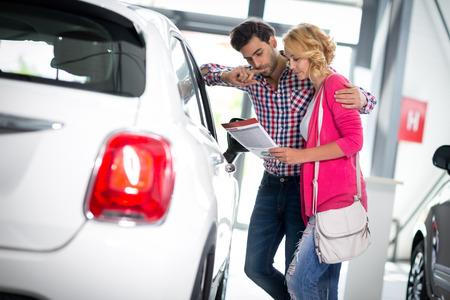 carro supermercado: feliz pareja opta por comprar un coche en salón Foto de archivo