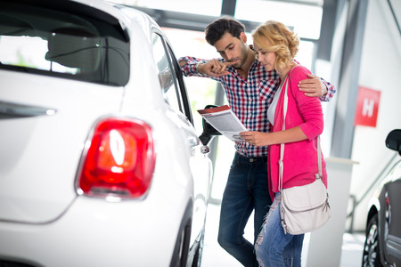 new car: Happy couple chooses to buy a car in showroom
