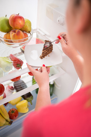 eat right: Close up young woman on diet stealing from fridge piece of nice chocolate cake Stock Photo