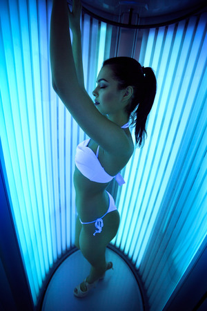 Young sexy female in a tanning cabin of modern solarium