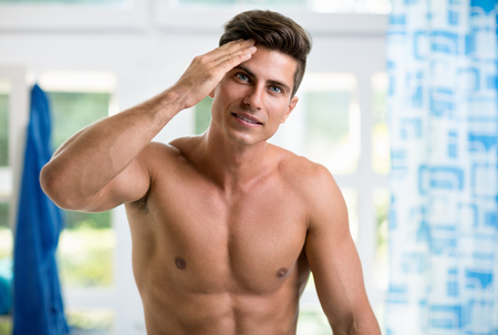 skincare: Handsome young man touching his hair with hand and smiling while standing in front of the mirror