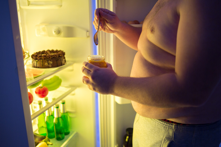 unhealthy: Close up of fat man break diet and takes at night dangerous unhealthy sweet from fridge Stock Photo