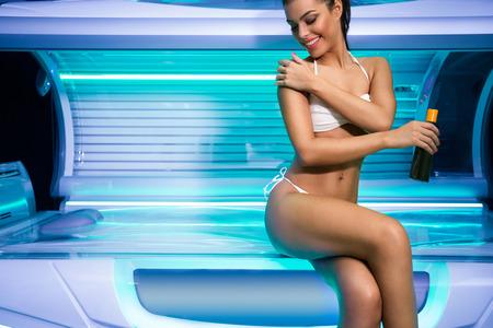 mujer en la cama: Atractiva joven se prepara para bronceado en las solanas, usando crema solar antes de bronceado Foto de archivo