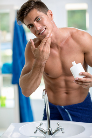 aftershave: Young man applying after shave,  portrait of a young handsome man with a skin for shaving Stock Photo