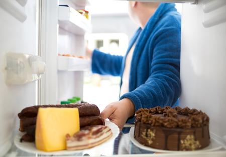 太りすぎの男はソーセージとチーズの代わりに健康的な簡単な食糧のようなハードの食事を取る 写真素材