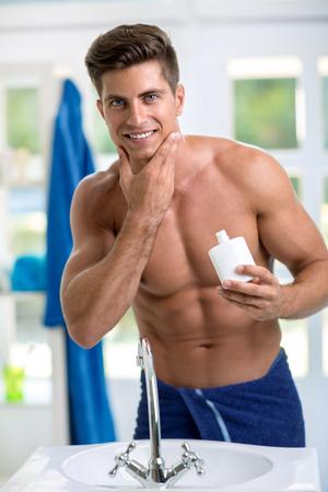 hombre fuerte: Sonriente hombre guapo aplicar después del afeitado en la piel de la barba Foto de archivo
