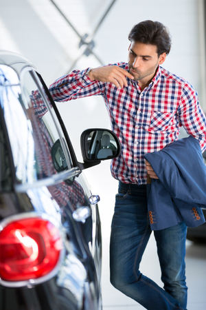 new car: Interested man  examines a new car in showroom, leaning against it watch at the interior of a new car Stock Photo