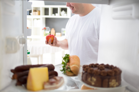 high calorie: Obese man take apple from fridge instead of high calorie meal from fridge