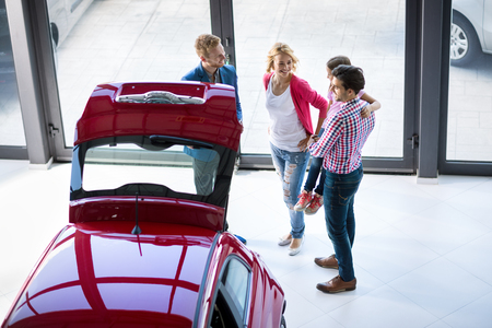 Car dealer offering a vehicle to young couple with daughter Stock Photo