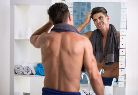 Man in the bathroom looking in a mirror and fixing his hair. Stock Photo