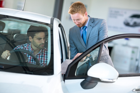 new car: Car agent and customer in car showroom,  together watching the performance of vehicle Stock Photo