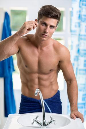 cuerpo hombre: Hombre que quita pelos de las cejas con pinzas