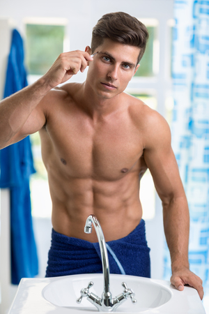 fit man: Man removing eyebrow hairs with tweezing Stock Photo