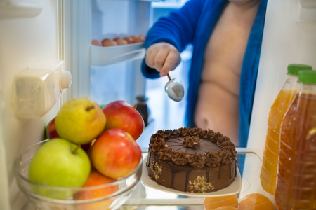 ordeal: Tasteful attractive chocolate cake in refrigerator is big ordeal for gourmet man Stock Photo