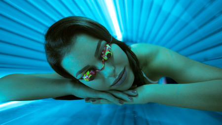 tanning: Woman in bed solarium with protect glasses