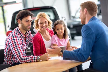 Glimlachend jong gezin met autohandelaar, concept koopt nieuwe auto