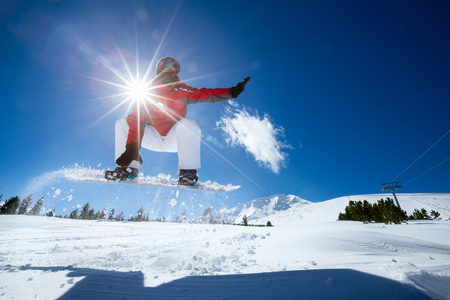 ski jump: Snowboarder in the air with beautiful  blue sky in background