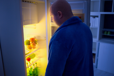 and the horizontal man: overweight guy at night open refrigerator looking for food