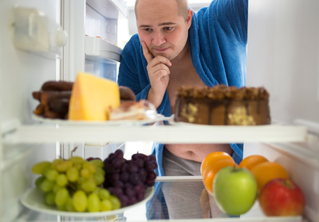 refrigerator with food: Corpulent man wish hard food rather than healthy food