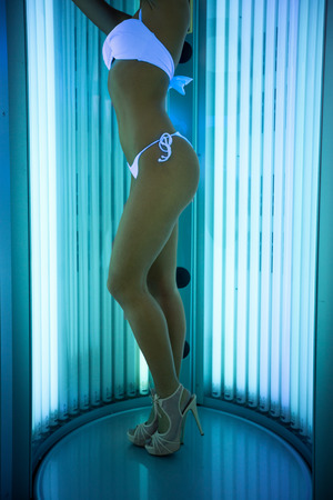 Attractive  woman dressed in swimsuit stands in solarium, full body