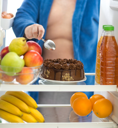 refrigerator with food: Obese guy prefer to eat big chocolate cake than fresh fruit in fridge