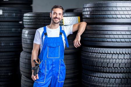 llantas: mecánico con neumáticos de coche en la tienda de neumáticos