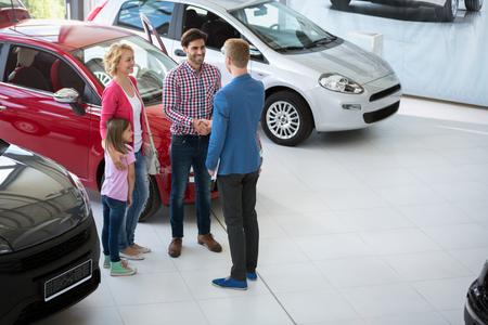 auto-agent handdruk met zijn vader en feliciteren met de familie op het kopen van auto