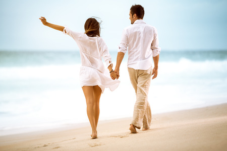 Happy couple on beach, attractive people walking