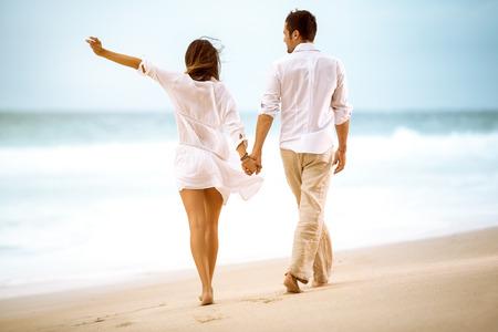 parejas caminando: Pareja feliz en la playa, la gente atractiva caminando