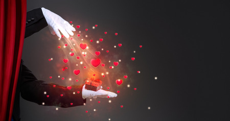 illusionist: Magician hand with sparkling surprise gift,  Valentines Day Stock Photo