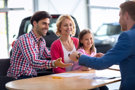 automobile sales: automobile sales center, car dealer selling new automobile to young family with child boy, giving key from the new car daddy