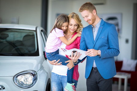 buy car: car dealer showing brochure young woman with child at car dealership saloon Stock Photo