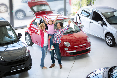 famille excité acheter une nouvelle voiture dans le salon concessionnaire automobile