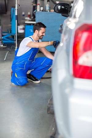 impact wrench: Mechanic mounted tire in workshop Stock Photo