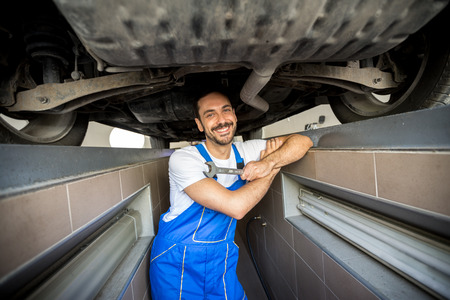 underneath: smiling mechanic underneath a car Stock Photo