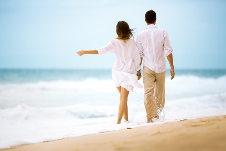 romantic beach: back view of happy romantic young couple walking at the beach Stock Photo