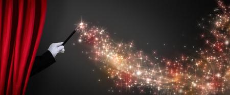 magia: La mano del mago con la varita mágica crea la ilusión