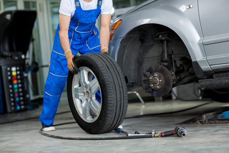 maintenance engineer: disc brake on car in process of new tire replacement Stock Photo