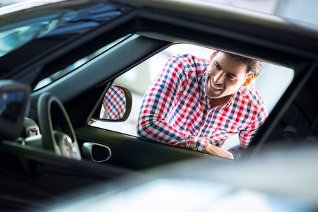 new car: smiling young man looking in interior of a new car Stock Photo