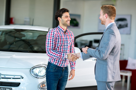 happy customer: Happy male customer handshake with car dealer