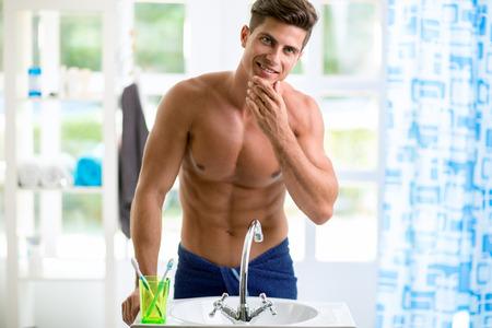 espejo: Hombre hermoso joven que se refleja en el espejo y comprueba la barba