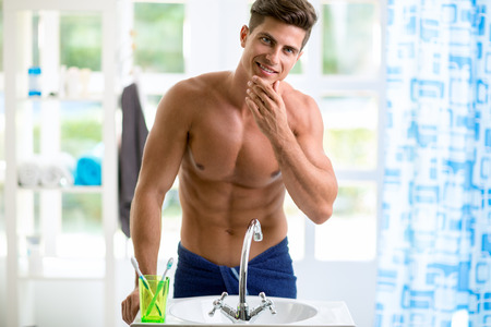 male grooming: Young handsome man is reflected in the mirror and checks his beard