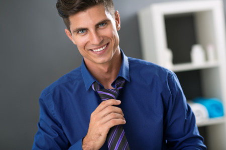 hurried: Young smiling man front mirror fixing tie Stock Photo