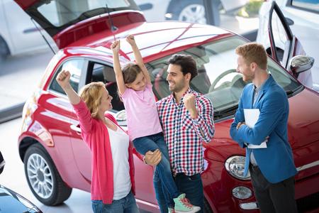 familias felices: Familia feliz y emocionado que celebra acaba de comprar un coche nuevo de concesionario