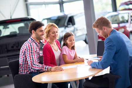 new automobile: car agent demonstrating new automobile to young family with child